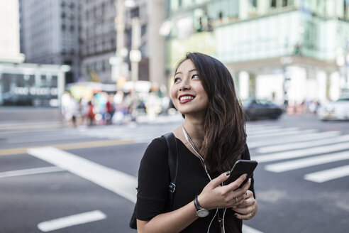 USA, New York City, Manhattan, young woman listening music with cell phone and earphones on the street - GIOF02489