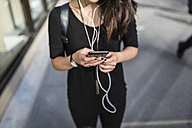 Young woman listening music with earphones while text messaging, partial view - GIOF02492