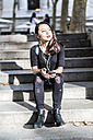 Portrait of young woman dressed in black sitting on steps listening music with earphones and cell phone - GIOF02495