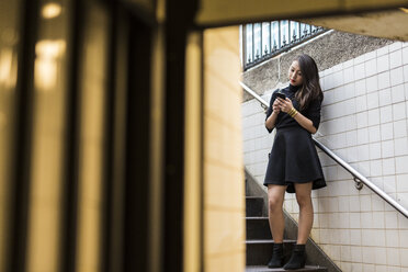 USA, New York City, Manhattan, young woman standing on stairs looking at smartphone - GIOF02504