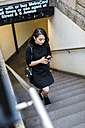 USA, New York City, Manhattan, young woman dressed in black walking upstairs looking at cell phone - GIOF02507