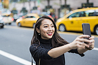 USA, New York City, Manhattan, portrait of smiling young woman taking selfie with smartphone - GIOF02510