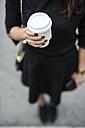 Woman's hand holding coffee to go - GIOF02513