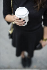 Woman's hand holding coffee to go - GIOF02513