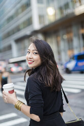 USA, New York City, Manhattan, portrait of smiling young woman with coffee to go crossing the street - GIOF02516