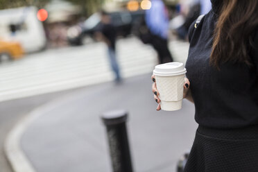 Woman with coffee to go the street, partial view - GIOF02519
