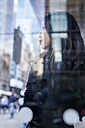 USA, New York City, Manhattan, daydreaming young woman behind glass pane - GIOF02522