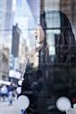 USA, New York City, Manhattan, daydreaming young woman behind glass pane - GIOF02522