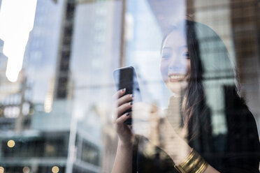 USA, New York City, Manhattan, smiling young woman behind glass pane looking at cell phone - GIOF02525
