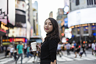 USA, New York City, Manhattan,  young woman with coffee to go on  the street - GIOF02531