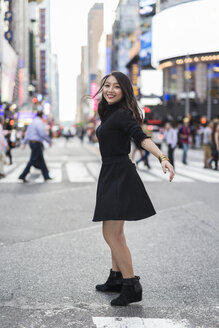USA, New York City, Manhattan, happy young woman dressed in black dancing on the street - GIOF02534