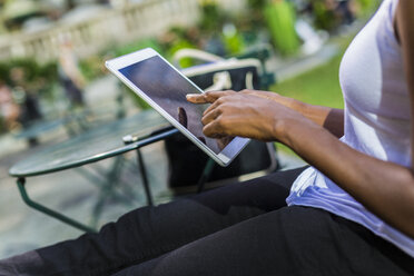 Woman sitting in a park using tablet, partial view - GIOF02537