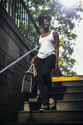 Portrait of smiling woman walking down stairs - GIOF02543