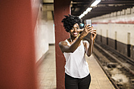 USA, New York City, Manhattan, smiling woman taking selfie at subway station platform - GIOF02546