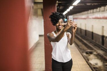 USA, New York City, Manhattan, smiling woman taking selfie at subway station platform - GIOF02546