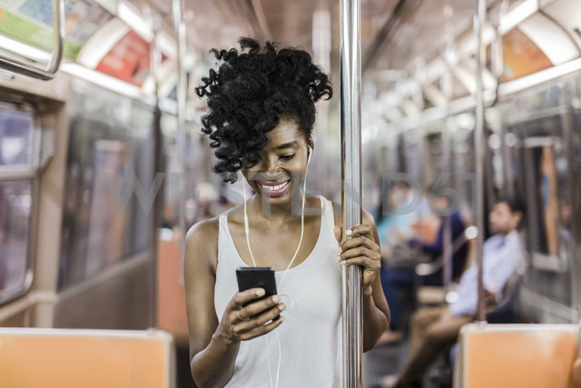 USA, New York City, Manhattan, portrait of happy woman looking at cell phone in underground train - GIOF02549