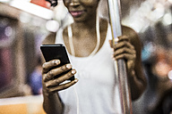 Woman's hand holding cell phone in underground train - GIOF02552