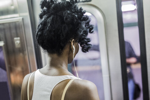 Back view of woman with earphones  in underground train - GIOF02555