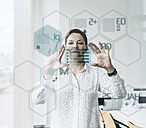 Businesswoman touching glass pane with data in office - UUF10234