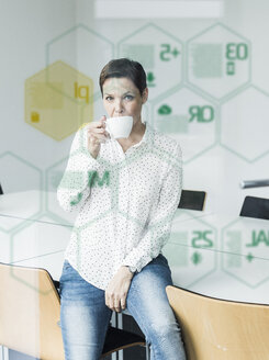 Businesswoman behind glass pane with data in office - UUF10237
