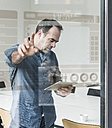 Businessman with tablet touching glass pane with data in office - UUF10240