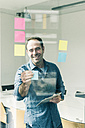 Smiling businessman with tablet and adhesive notes in office - UUF10258