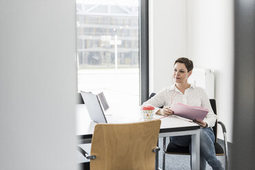 Businesswoman having a video conference in office - UUF10282
