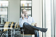 Happy businessman using cell phone and tablet in office - UUF10285