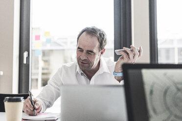 Businessman working at desk in office - UUF10294