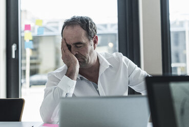 Exhausted businessman sitting at desk in office - UUF10297