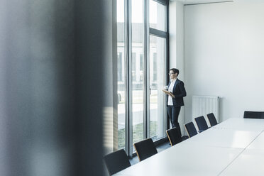 Businesswoman looking out of office window - UUF10306