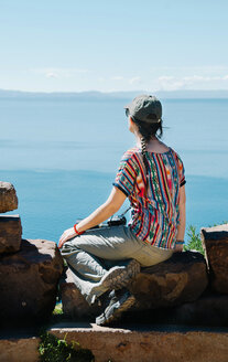 Peru, Taquile, back view of woman sitting on a rock enjoying view over Titicaca lake - GEMF01553