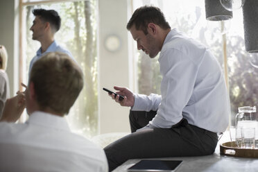 Businessman using smart phone in a meeting - ZEF13278