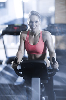 Portrait of smiling woman on spinning bike in gym - ZEF13322
