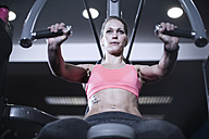 Focused woman using chest exercise equipment at gym - ZEF13325