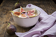 Bowl of overnight oats with blueberry yoghurt and figs on wood - LVF05958