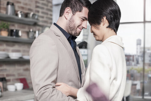 Smiling couple embracing at home - ZEF13343
