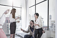 Couple and friends having champagne in open plan apartment with city view - ZEF13349