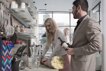 Man and woman with bunch of flowers and wine bottle in kitchen - ZEF13358