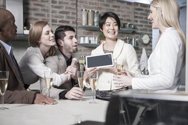 Happy woman showing tablet to friends with champagne glasses at home - ZEF13364