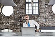 Portrait of confident businessman with laptop sitting at table in a loft - FMKF03659