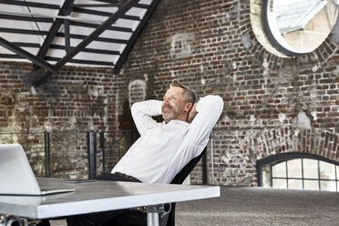 Smiling businessman sitting at table in a loft leaning back - FMKF03665