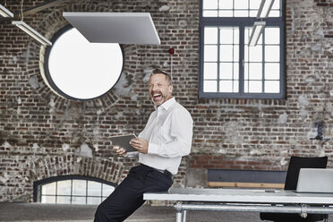 Laughing businessman with tablet in a loft - FMKF03668