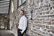 Portrait of happy businessman leaning against brick wall - FMKF03671