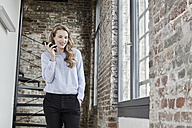 Smiling businesswoman at brick wall using cell phone - FMKF03692