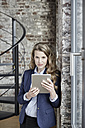 Portrait of confident businesswoman holding tablet - FMKF03695