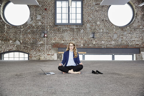 Barefeet businesswoman sitting on the floor in a loft next to laptop - FMKF03704