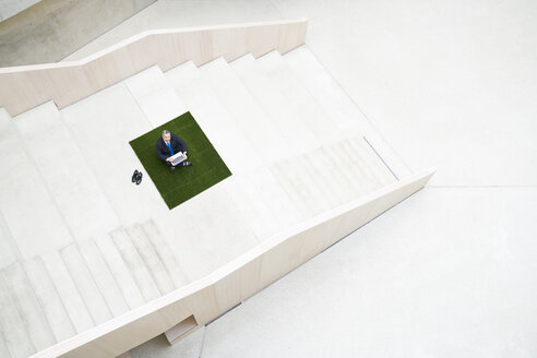 Top view of businesssman on stairs using laptop - FMKF03710