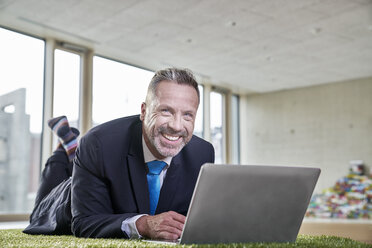 Happy businesssman lying on synthetic turf using laptop - FMKF03713