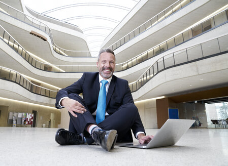 Happy businesssman sitting on floor in modern office building using laptop - FMKF03716